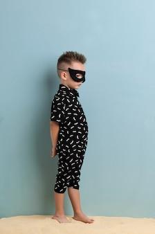 Mały chłopiec w czarnym garniturze i masce stojący na piasku na jasnoniebieskim tle