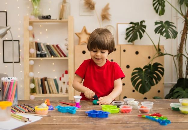 Mały chłopiec w czerwonej koszulce bawi się plasteliną na drewnianym stole z papeterią