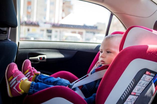 Mały chłopiec w czerwonym foteliku samochodowym. małe dziecko w dżinsach, dzianinowej kurtce i trampkach siedzi na siedzeniu samochodu. bezpieczeństwo transportu dzieci w samochodzie.