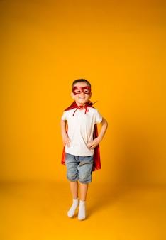 Mały chłopiec w czerwonym garniturze skacze na żółtej powierzchni z miejscem na tekst