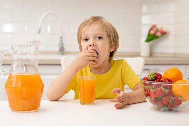 Mały chłopiec w domu, jedzenie owoców