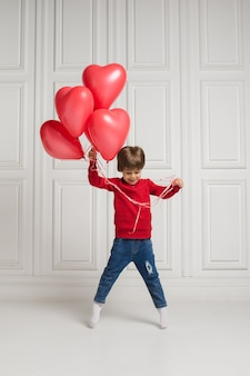 Mały chłopiec w dżinsach i swetrze skacze z czerwonymi balonami na białym tle z miejscem na tekst