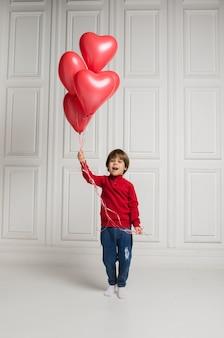 Mały chłopiec w dżinsach i swetrze, zabawy z czerwonymi balonami na białym tle z miejscem na tekst