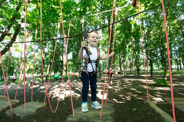 Mały chłopiec w ekwipunku wspinaczkowym idzie wzdłuż drogi linowej w parku przygód, trzymając się liny i karabińczyka.