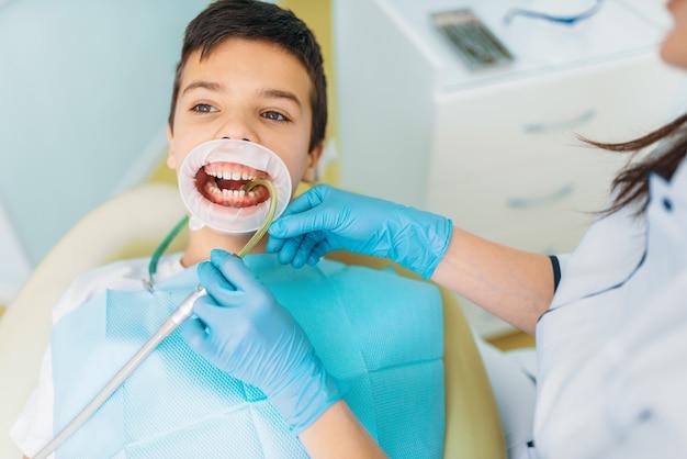 Mały chłopiec w gabinecie stomatologicznym, zabieg usuwania próchnicy