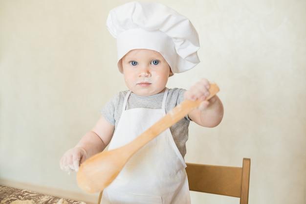 Mały chłopiec w garniturze kucharza rzeźbi ciasto. dziecko przygotuj obiad w garniturze szefa kuchni