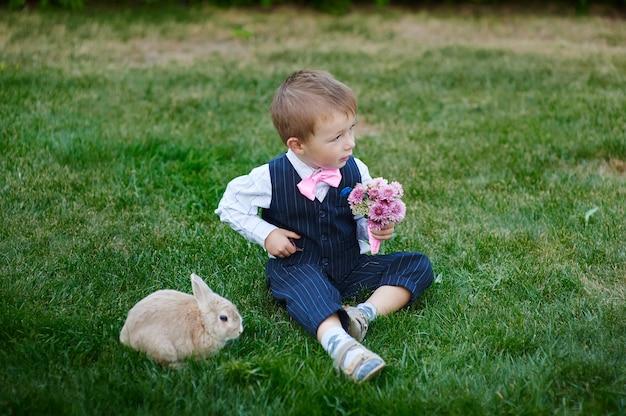 Mały chłopiec w garniturze z bukietem kwiatów i króliczkiem