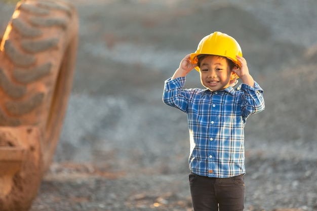 Mały chłopiec w hełmie, koncepcja marzeń, chce zostać przyszłym inżynierem.
