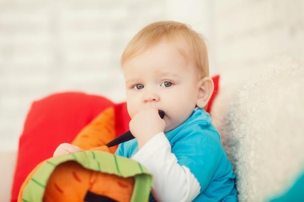 Mały chłopiec w jasnych ubraniach siedzi w pokoju