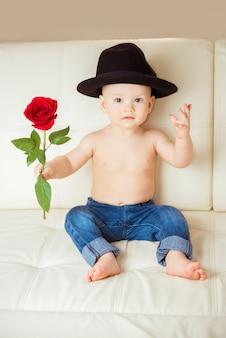 Mały chłopiec w kapeluszu z czerwoną różą