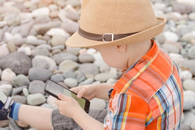 Mały chłopiec w kapeluszu z inteligentny telefon na kamienistej plaży