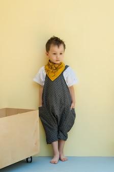 Mały chłopiec w kombinezonie z drewnianym pudełkiem na żółtym tle