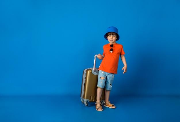 Mały chłopiec w koszulce, szortach i czapce panama stoi z walizką na niebieskiej powierzchni z miejscem na tekst