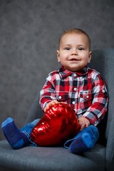 Mały chłopiec w koszuli bawi się balonem w kształcie serca