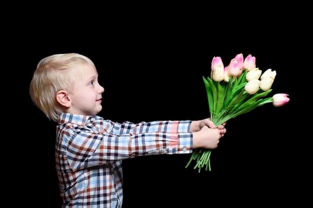 Mały chłopiec w koszuli daje bukiet tulipanów.
