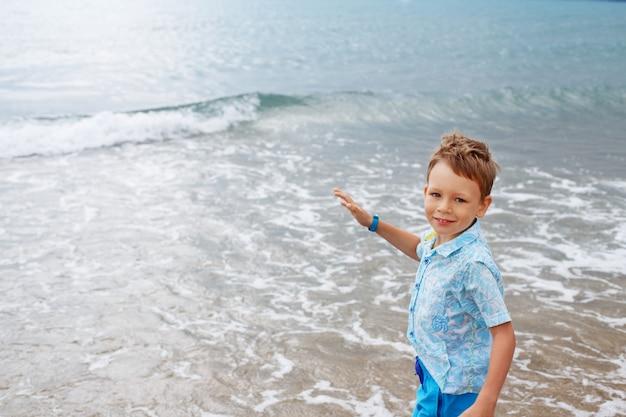 Mały chłopiec w koszuli i spodenkach na piasku plaży.
