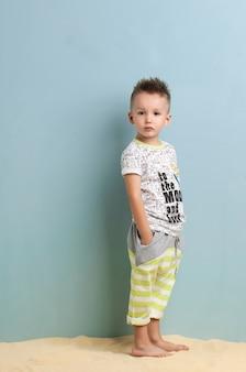 Mały chłopiec w koszuli i spodenkach stojący na piasku na jasnoniebieskim tle
