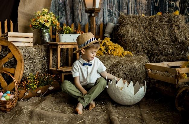 Mały chłopiec w koszuli z muszką i słomkowym kapeluszu siedzi na słomie i patrzy na muszlę z kaczuszkami. wielkanoc dla dzieci