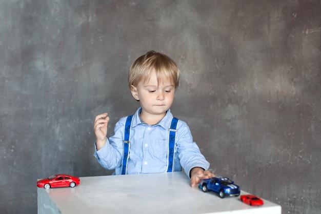 Mały chłopiec w koszuli z szelkami bawi się zabawkowymi wielobarwnymi samochodzikami. chłopiec w wieku przedszkolnym, grając z autko na stole w domu lub przedszkola. zabawki edukacyjne dla dzieci w wieku przedszkolnym i przedszkolnym.