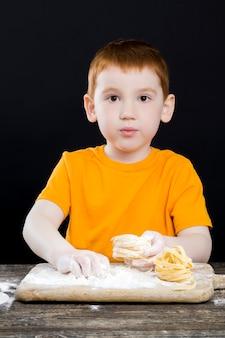 Mały chłopiec w kuchni podczas gotowania, piękny chłopiec o rudych włosach i pięknych rysach twarzy, dziecko bawiące się mąką w kuchni i wszystko posmarowane mąką w proszku