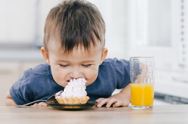 Mały chłopiec w kuchni zjada ciasto, próbując wsadzić je sobie do ust bez rąk