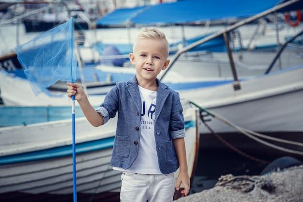 Mały chłopiec w marynistycznym stylu na tle łodzi i jachtów. pomysł i koncepcja przyjaźń, wakacje, wakacje, rodzina