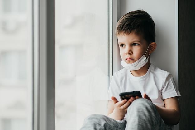 Mały chłopiec w masce medycznej siedzi w oknie domu w kwarantannie z telefonem w rękach. zapobieganie koronawirusowi i covidowi - 19