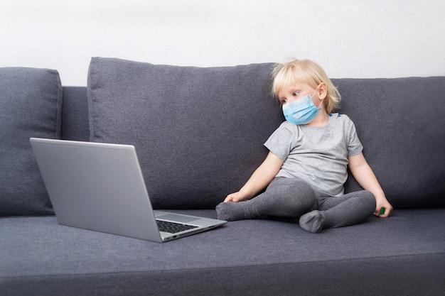 Mały chłopiec w masce oddechowej zostaje w kwarantannie w domu i ogląda bajki na laptopie