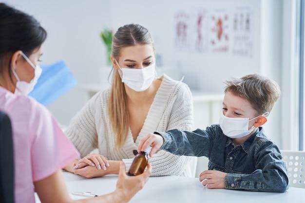 Mały chłopiec w masce poddawany badaniu lekarskiemu przez pediatrę podczas pandemii