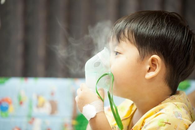Mały chłopiec w masce tlenowej na oddziale szpitalnym