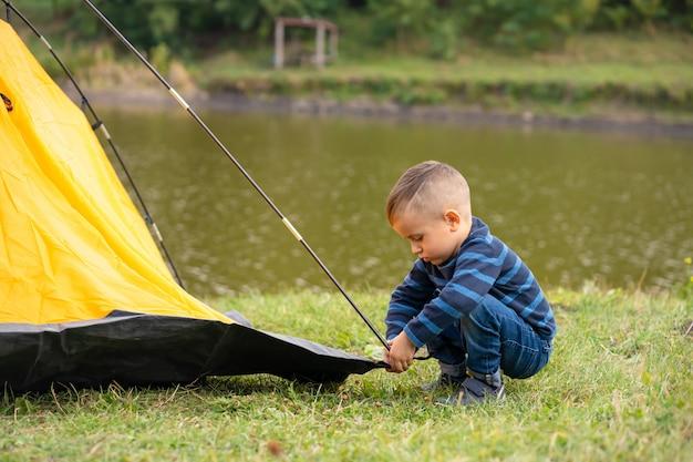 Mały chłopiec w namiocie. camping na łonie natury.