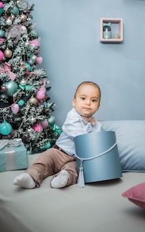 Mały chłopiec w niebieskiej koszuli siedzi w pokoju na łóżku z prezentem na choince