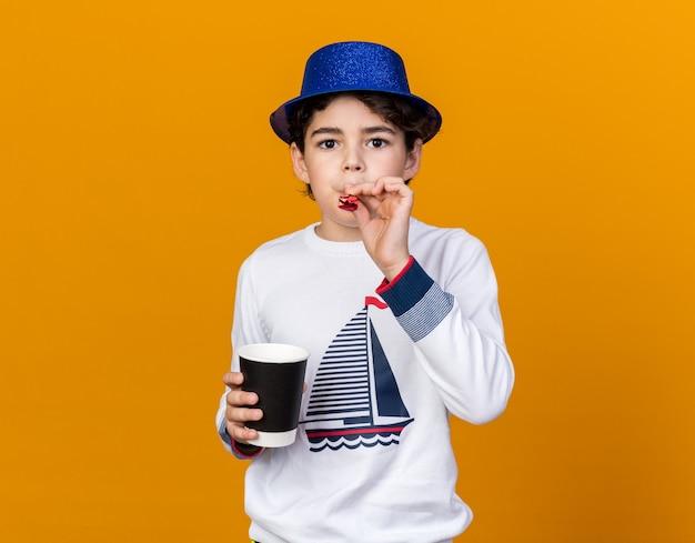Mały chłopiec w niebieskim kapeluszu imprezowym dmuchający gwizdek trzymający filiżankę kawy odizolowaną na pomarańczowej ścianie