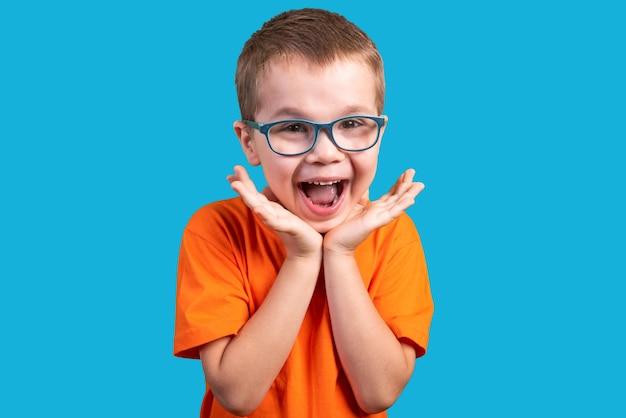 Mały chłopiec w okularach jest bardzo zaskoczony. na białym tle na niebieskim tle. w dowolnym celu.