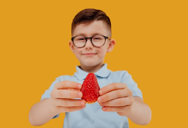 Mały chłopiec w okularach trzyma w ręku truskawkę odizolowaną na żółtym tle