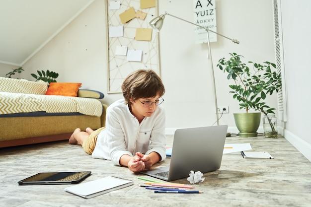 Mały chłopiec w okularach uczący się online leżąc na drewnianej podłodze i korzystający z laptopa