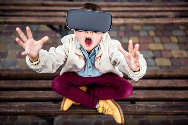Mały chłopiec w okularach wirtualnej rzeczywistości w parku