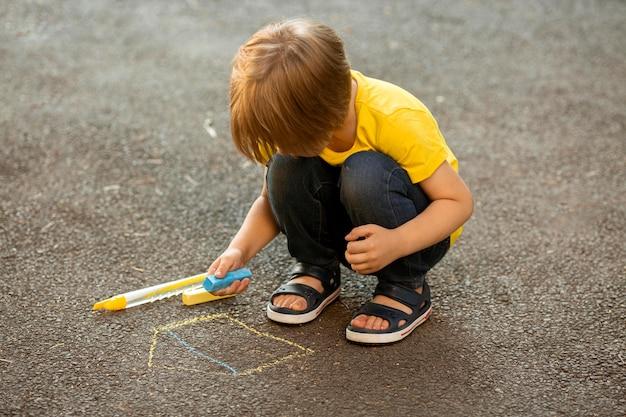 Mały chłopiec w parku, rysowanie kredą