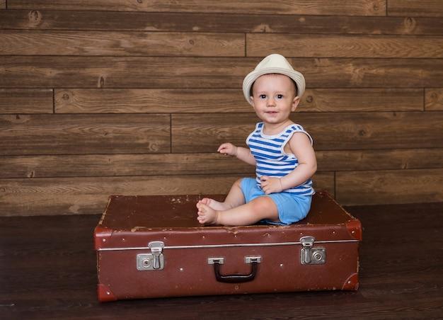 Mały chłopiec w pasiastej koszulce i słomkowym kapeluszu siedzi na walizce retro na drewnianej powierzchni z miejscem na tekst
