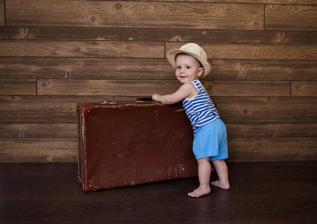 Mały chłopiec w pasiastej koszulce i słomkowym kapeluszu stoi z walizką retro na drewnianej powierzchni z miejscem na tekst