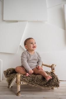 Mały chłopiec w pasiastym body, siedzący na małym drewnianym łóżku