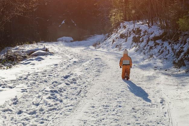 Mały chłopiec w pomarańczowym kombinezonie chodzącym po zaśnieżonej drodze w lesie iglastym. zimowy słoneczny dzień. widok z tyłu.
