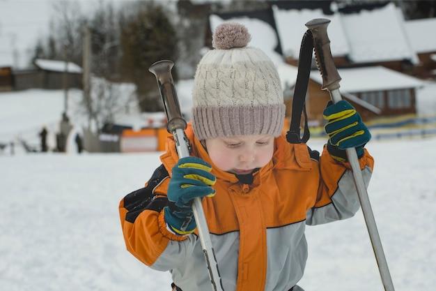 Mały chłopiec w pomarańczowym kombinezonie stoi z kijkami narciarskimi. zimowy dzień.