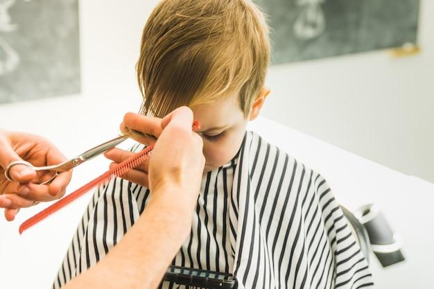 Mały chłopiec w salonie fryzjerskim