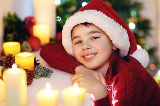 Mały chłopiec w santa hat przy kominku w pokoju