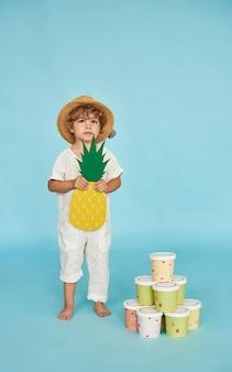 Mały chłopiec w słomkowym kapeluszu stoi obok wielokolorowych ekologicznych kubków na niebieskim tle. koncepcja ochrony ekologii dla naszych dzieci.