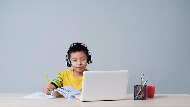 Mały chłopiec w słuchawkach studiuje online za pomocą laptopa
