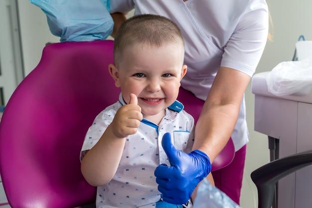 Mały chłopiec w stomatologii, uśmiechając się i pokazując kciuk do góry