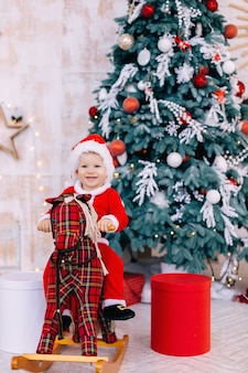 Mały chłopiec w stroju mikołaja na koniu na biegunach z choinką i prezentami.