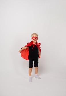 Mały chłopiec w stroju superbohatera na białym tle